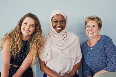 Buy stock photo Portrait of a group of cheerful businesswomen waiting in a line while being seated against a grey background