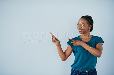 Buy stock photo Portrait of a cheerful young businesswoman pointing to a certain direction while standing against a grey background