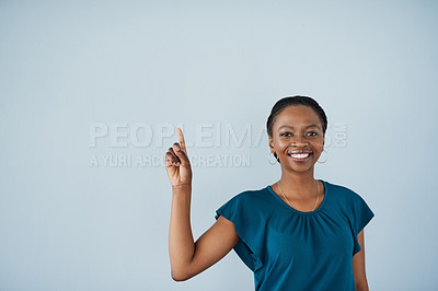 Buy stock photo Portrait of a cheerful young businesswoman holding up her finger so that she can ask a question while standing against a grey background
