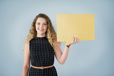 Buy stock photo Portrait of a cheerful young businesswoman holding a colorful speech bubble while standing against a grey background