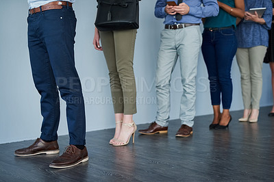 Buy stock photo Studio shot of a group of unrecognizable businesspeople using their wireless devices while waiting in a line