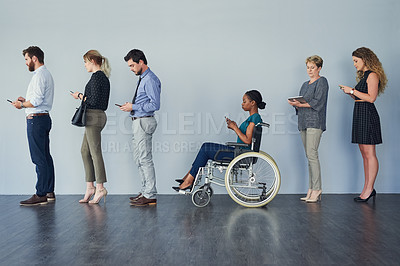 Buy stock photo Studio shot of a group of  businesspeople using their wireless devices while waiting in a line