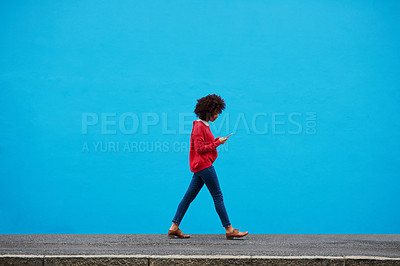 Buy stock photo Shot of a fashionable young woman using her cellphone while walking through the city