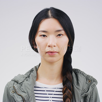 Buy stock photo Studio portrait of an attractive young woman posing expressionless against a grey background