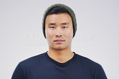 Buy stock photo Studio portrait of a handsome young man posing expressionless against a grey background