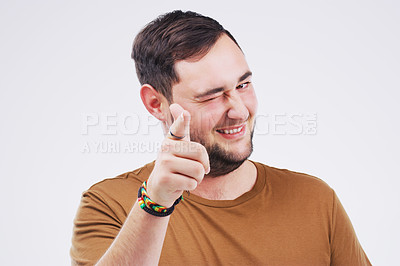 Buy stock photo Portrait of a handsome young man winking and pointing to the camera against a grey background