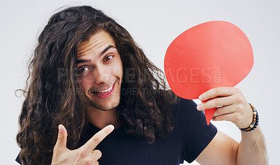 Buy stock photo Portrait of a handsome young man holding a speech bubble against a grey background