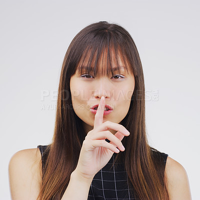 Buy stock photo Portrait of an attractive young woman posing with her finger on her lips against a grey background
