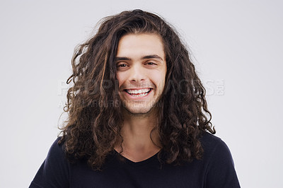 Buy stock photo Studio portrait of a handsome young man smiling against a grey background