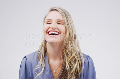Buy stock photo Studio shot of an attractive young woman laughing while standing against a grey background