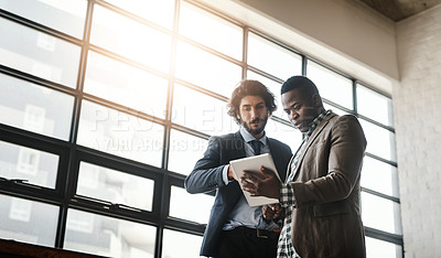 Buy stock photo Low angle shot of two well-dressed businessmen brainstorming together over a tablet in their office