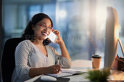 Buy stock photo Shot of a young businesswoman talking on a cellphone while working in an office at night