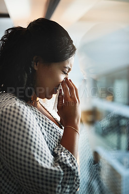 Buy stock photo Shot of a young businesswoman blowing her nose in an office at night