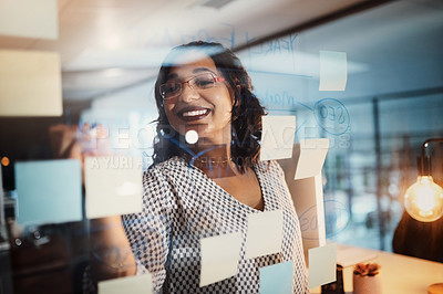Buy stock photo Shot of a young businesswoman writing notes on a glass wall in an office