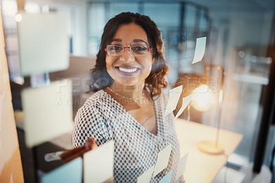 Buy stock photo Portrait of a young businesswoman writing notes on a glass wall in an office