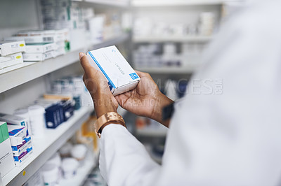 Buy stock photo Cropped shot of an unrecognizable pharmacist picking medication from the shelves
