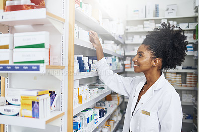 Buy stock photo Cropped shot of a female pharmacist taking a product from the shelves