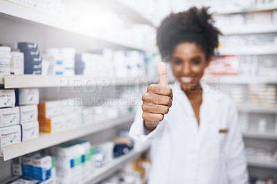 Buy stock photo Shot of a confident young pharmacist showing thumbs up in a chemist