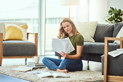 Buy stock photo Full length shot of an attractive young woman looking over her home finances while sitting on the floor at home