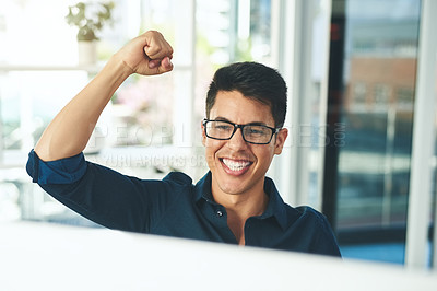 Buy stock photo Shot of a happy young businessman celebrating at his desk in a modern office