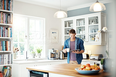 Buy stock photo Shot of a middle aged man using a digital tablet at home