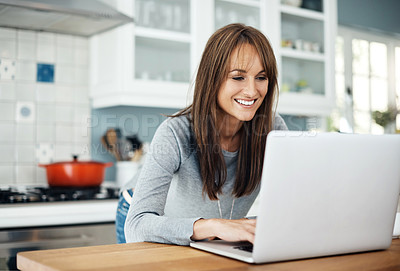 Buy stock photo Cropped shot of a middle aged woman using her laptop while relaxing at home