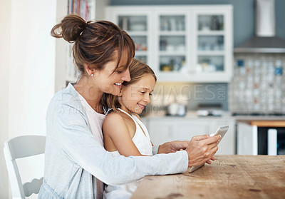 Buy stock photo Shot of a little girl sitting on her mother's lap while using a digital tablet