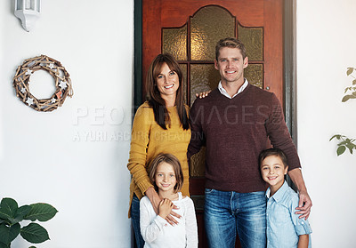 Buy stock photo Portrait of a happy family standing together outside their house