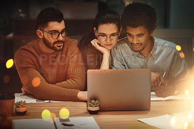 Buy stock photo Shot of a group of businesspeople working together on a laptop in an office at night