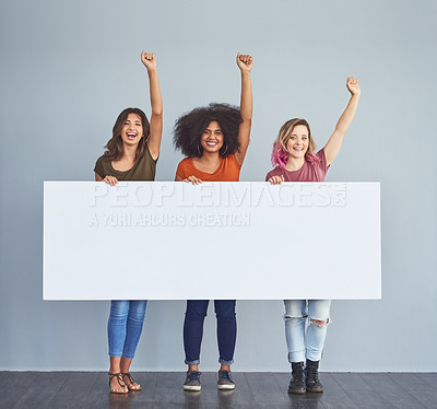 Buy stock photo Studio shot of a group of young women holding a blank placard and cheering against a gray background