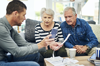 Buy stock photo Shot of senior couple using a smartphone during a consultation with a financial advisor at home