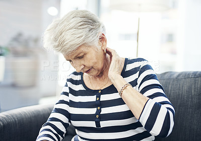 Buy stock photo Shot of a senior woman experiencing neck pain at home