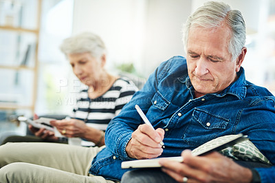 Buy stock photo Shot of a senior couple managing their finances together at home