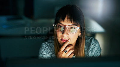 Buy stock photo High angle shot of an attractive young businesswoman looking thoughtful while working on her computer late at night in the office