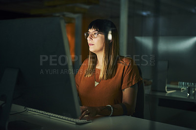 Buy stock photo Cropped shot of an attractive young businesswoman working on a computer late at night in her office