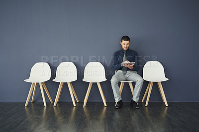Buy stock photo Studio shot of a handsome businessman waiting in line for an interview against a grey background