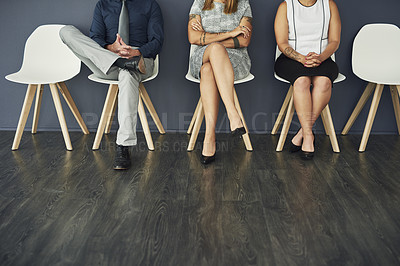 Buy stock photo Studio shot of a group of confident businesspeople waiting for an interview while being seated against a grey background