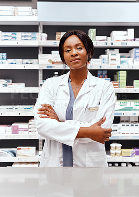 Buy stock photo Cropped portrait of an attractive young female chemist standing with her arms crossed in the pharmacy