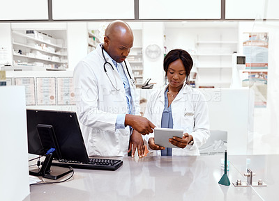 Buy stock photo Cropped shot of two young chemists working behind a counter in the pharmacy