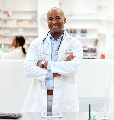 Buy stock photo Cropped portrait of a handsome young male chemist standing with his arms crossed in the pharmacy with a colleague in the background