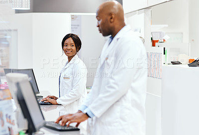 Buy stock photo Cropped shot of an attractive young female chemist talking to a male colleague while working in the pharmacy