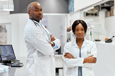 Buy stock photo Cropped portrait of two young chemists standing with their arms crossed in the pharmacy