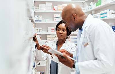Buy stock photo Cropped shot of two young chemists doing stock take while working in the pharmacy