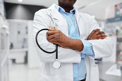 Buy stock photo Cropped shot of an unrecognizable male pharmacist holding a stethoscope with his arms crossed in the pharmacy