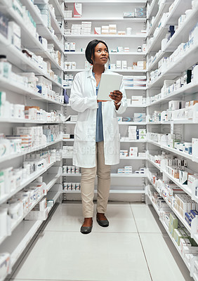 Buy stock photo Full length shot of an attractive young female chemist doing stock take while working in the pharmacy