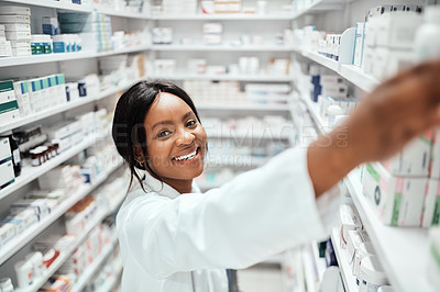 Buy stock photo High angle portrait of an attractive young female chemist doing stock take while working in the pharmacy