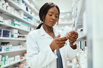 Buy stock photo Cropped shot of an attractive young female chemist doing stock take while working in the pharmacy
