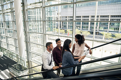 Buy stock photo High angle shot of a group of businesspeople talking while going up an escalator in their office