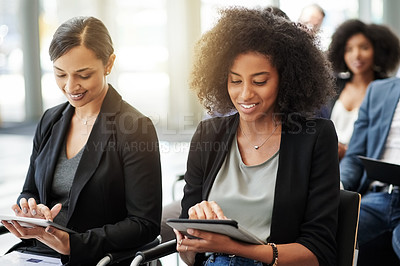 Buy stock photo Shot of a businesswoman using a digital tablet during a conference