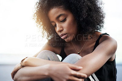 Buy stock photo Shot of a young woman suffering from depression at home